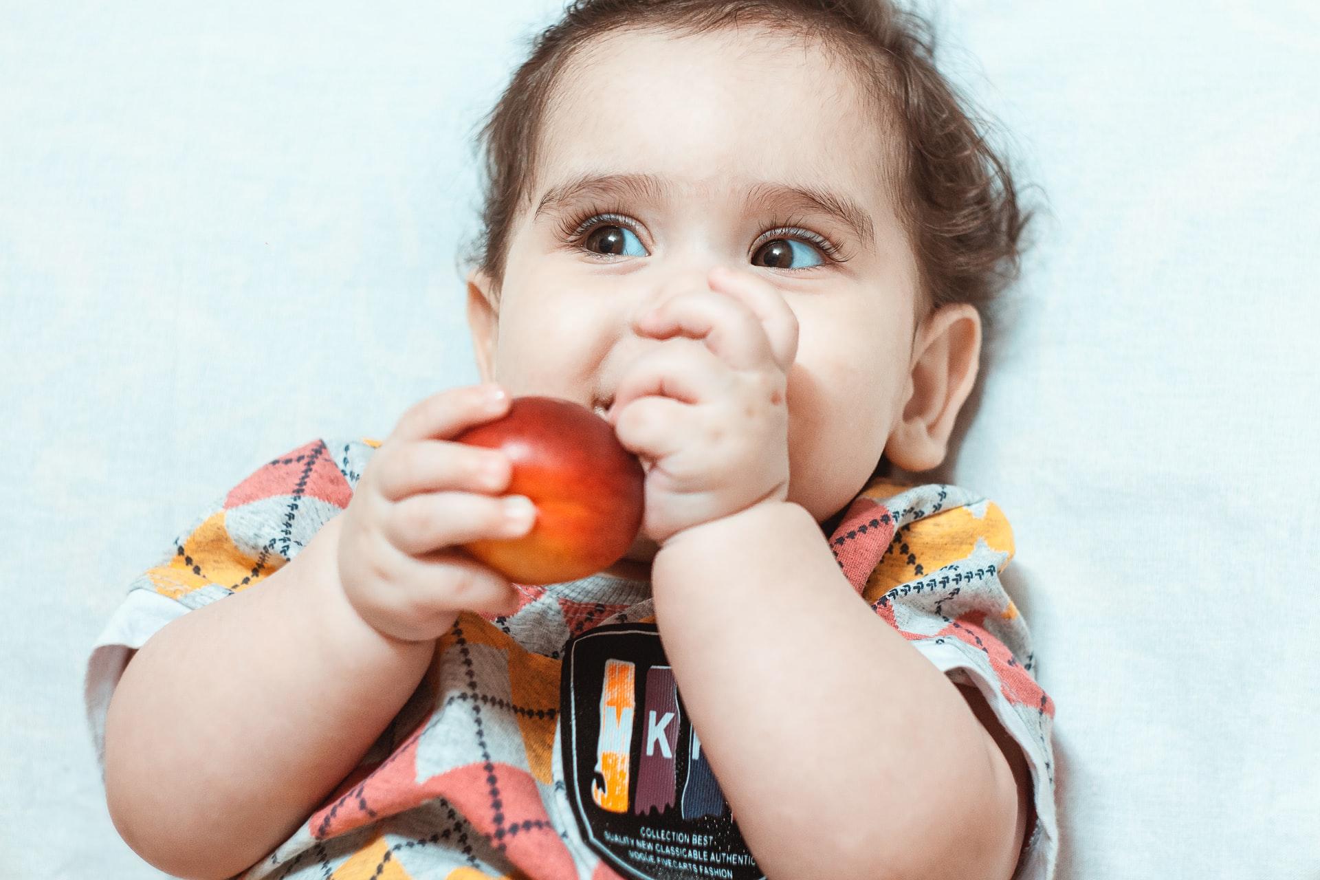 bayi memegang buah dengan tangannya